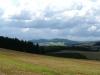 und diese nach Westen auf den Höhenzug der Wildenburg. Das Dorf hinten vor dem Höhenzug ist Mörschied, die Häuser rechts gehören zu Breitenthal.
